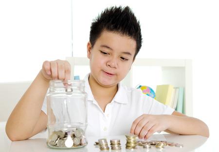 Asian boy putting coins into the glass bottle. money saving concept. Standard-Bild