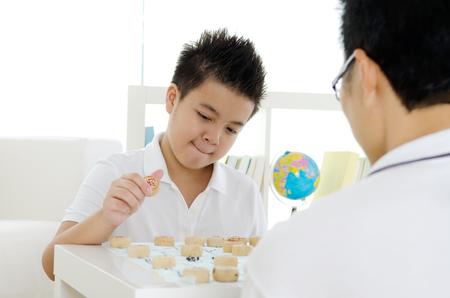 jugando ajedrez: Muchacho asiático y su padre jugando al ajedrez chino en casa
