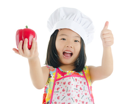 eating up: Asian girl holding a capsicum and thumbs up. healthy eating concept Stock Photo