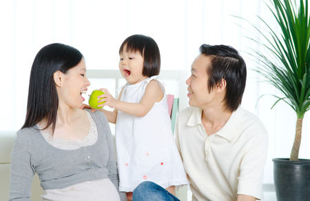 Lovely asian child feeding her pregnant mother with apple photo