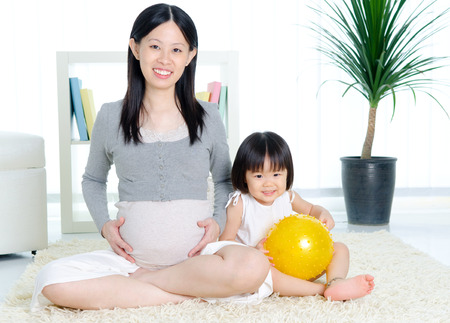maternal: Asian pregnant woman daughter sitting on the floor