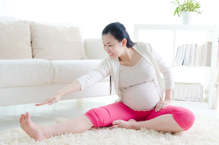 pregnancy yoga: Pregnant woman exercise Stock Photo