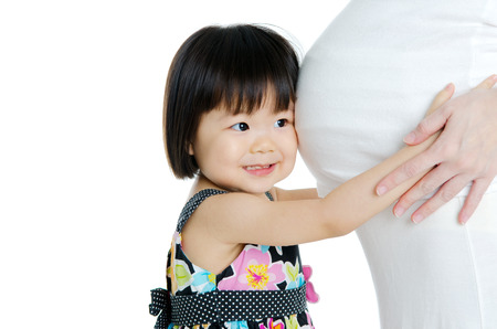 Cute little asian girl listening to her pregnant mother\ photo