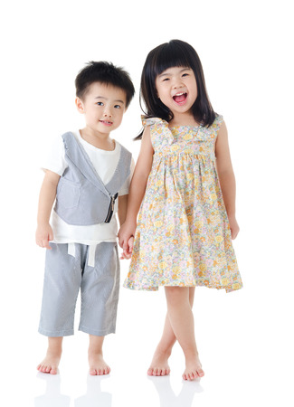 Asian kids standing and holding hands