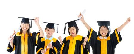 graduado: Grupo de ni�os de escuela excitados en traje de graduaci�n