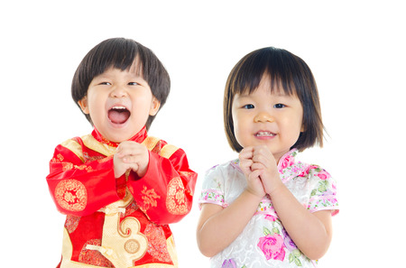 chinese people: Little asian kids in greeting gesture. Chinese new year concept.