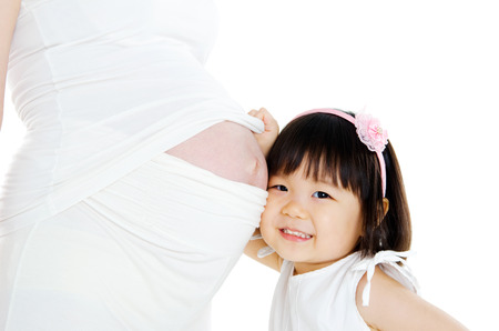Asian girl listening to her pregnant mother\\ Stock Photo
