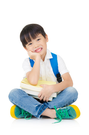 Asian preschool boy with schoolbag and books sitting on the floor Фото со стока