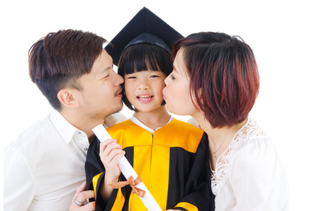 mother board: kindergarten kid kissed by her parent on her graduation day. Stock Photo