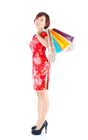 Beautiful asian woman in traditional cheongsam cloth carrying shopping bags. photo