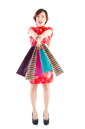 Asian woman in traditional cheongsam cloth holding shopping bags. Festive shopping concept. photo