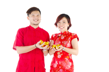 ingots: Asian couple in traditional cheongsam cloths holding gold ingots. Chinese new year concept.