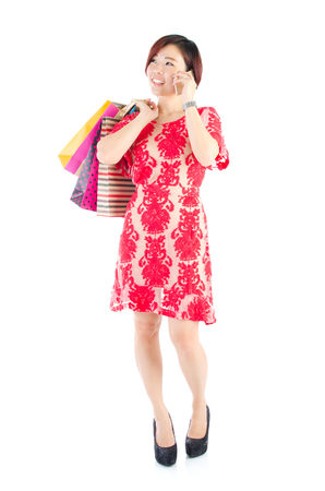 Modern asian woman carrying shopping bags and talking on the cellphone photo
