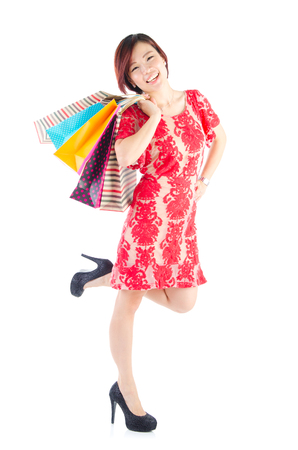 Excited asian woman carrying shopping bags photo