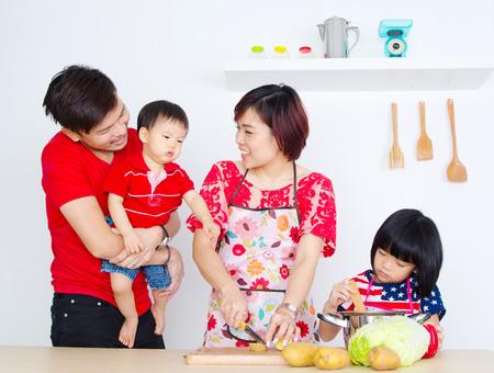 happy family: Familia asi�tica en la cocina