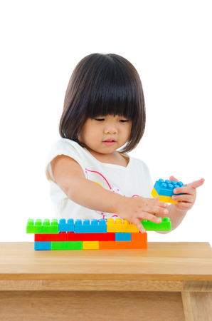 piling: Asian kid piling up building blocks