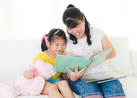 Asian mother reading story to daughter Standard-Bild
