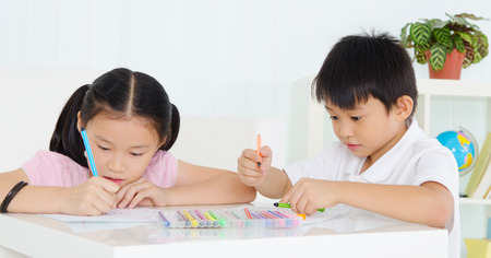 Asian kids drawing with coloured pencils Stock Photo
