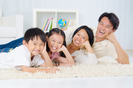 Beautiful asian family lying on the floor and laugh