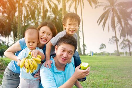 comiendo frutas: Familia asiática disfrutar de la naturaleza al aire libre Foto de archivo