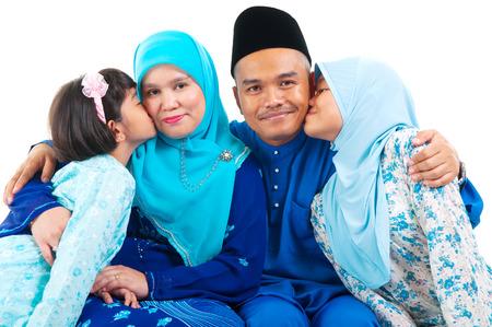 Malay girls kiss their parent