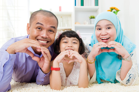 girl care: Malay family making love shape with hands