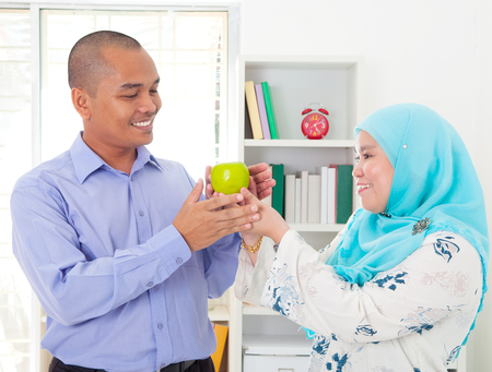 malay food: Malay woman giving an apple to her husband. Healthy eating concept