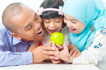 Malay family eating apple