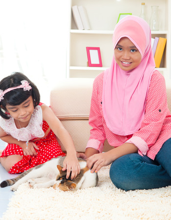 malaysian people: Malays girls playing with cat at home