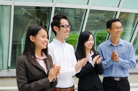 Asian business team clap hands