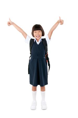 uniforme: Asia niña de la escuela primaria levantó sus pulgares. Concepto de la educación. Foto de archivo