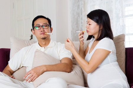 negligent: Smoking pregnant woman and husband sitting on sofa