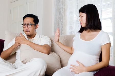 Asian man smoke in front of pregnant wife