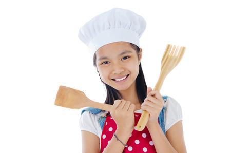 niños cocinando: Muchacha asiática que desgasta el delantal y la celebración de utensilios de cocina