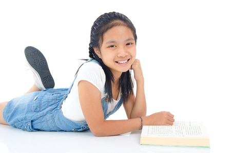 asian children: Asian girl lying on the floor and reading a book Stock Photo