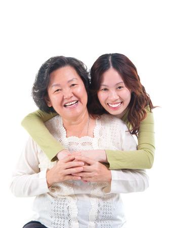 embrace family: Retrato de la mujer mayor asiática e hija