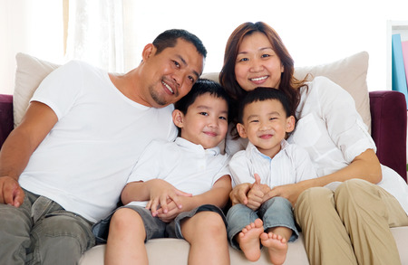 southeast asian: Portrait of asian family sitting on sofa