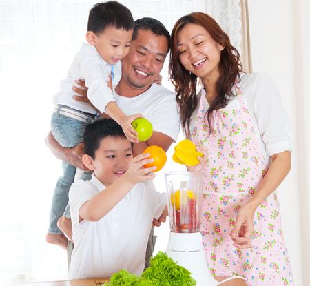 licuadora: Familia asiática preparar frutas y verduras jugo.