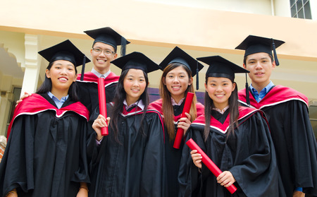 ceremonia: Grupo de estudiantes universitarios asiáticos en traje de graduación y birrete Foto de archivo