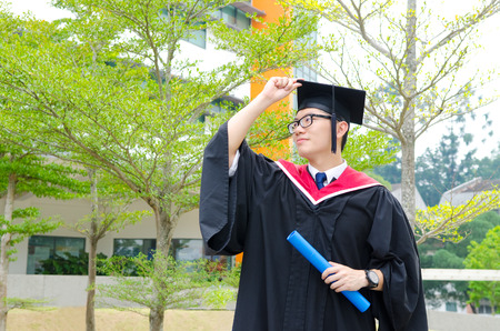 master degree: Asian university student in graduation gown and mortarboard Stock Photo