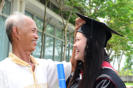 Asian man helping daughter to fix her mortarboard during graduation