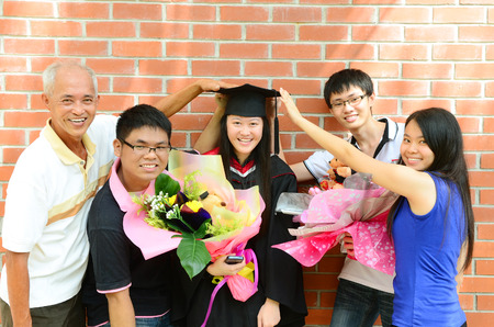 graduacion de universidad: Familia asiática celebrar la graduación de un familiar