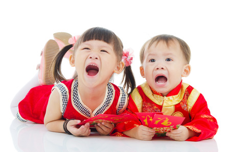 red packet: Asian kids in traditional chinese costume, cheongsam lying on the floor holding red packet