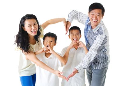 Aziatische familie die hartvorm met handen Stockfoto