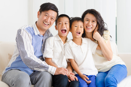 Asian family sitting on sofa photo