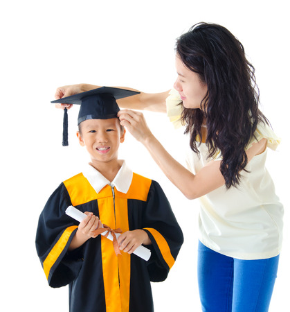 mom son: Asian kindergarten kid in graduation gown and mortarboard Stock Photo