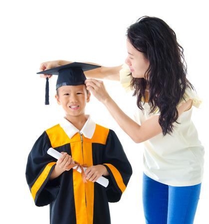 mama e hijo: Kindergarten asiática en traje de graduación y birrete Foto de archivo