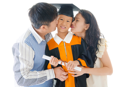 Asian kindergarten child in graduation gown and mortarboard kissed by her parent during graduation photo
