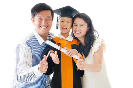 Asian kindergarten kid in graduation gown and mortarboard Stock Photo