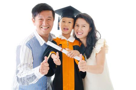 Asian kindergarten kid in graduation gown and mortarboard Standard-Bild